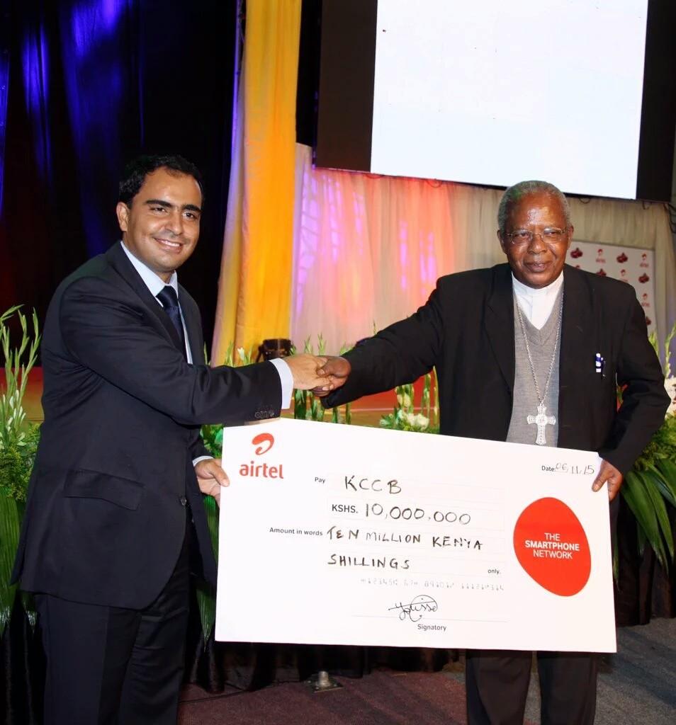 Airtel Kenya CEO Adil El Youssefi presents a cheque to Cardinal John Njue