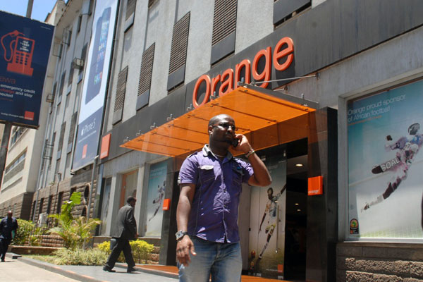 A man walks past an Orange Telkom shop on Koinange Street in Nairobi on June 17, 2013.  The company has announced yesterday that it has signed a binding agreement with Helios Investment Partners for the sale of its entire 70% stake in Telkom Kenya. Source; Daily Nation