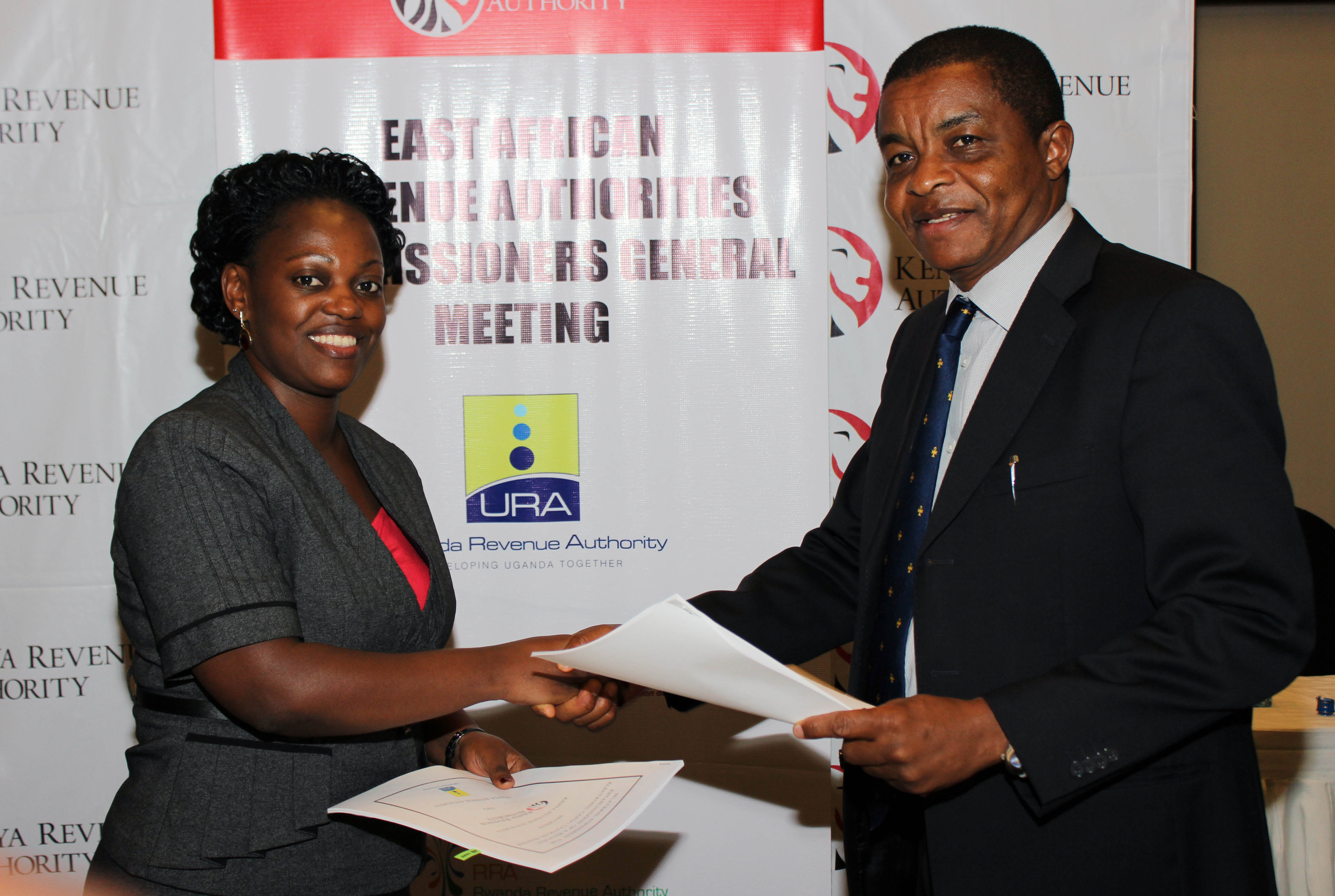 URA Legal Services Commissioner Patience Rubagumya exchanges documents with KRA boss Njiraini