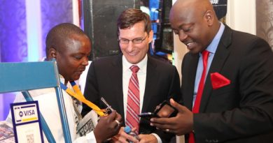 Andrew Torre (centre), Visa Sub Saharan Africa Group Country Manager demonstrates how the mVisa app works to KCB Group Head of Channels Retail Banking Dennis Njau (right), Looking on is newspaper vendor Humphrey Maina.