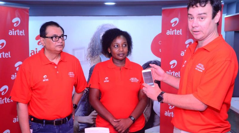 Airtel Kenya CEO, Prasanta Das Sarma and Director Legal and Regulatory Affairs, Joy Nyaga listen keenly as Ag. Marketing Director, Joep Verheij demonstrates how to subscribe to the newly launched Tubonge product.